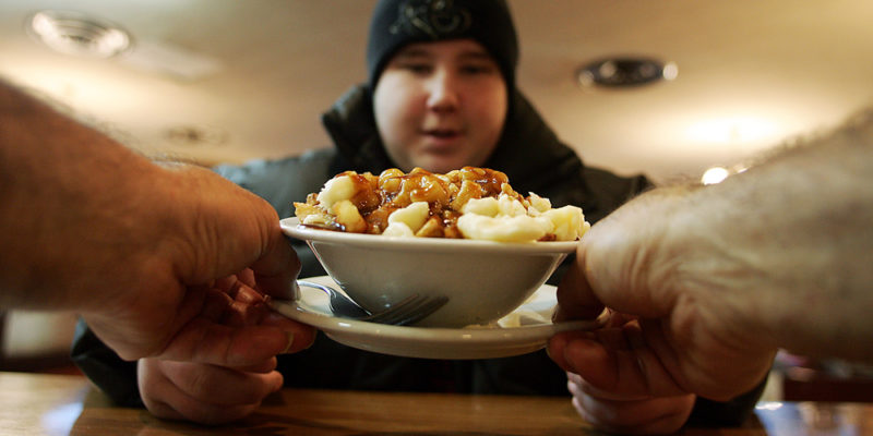 man waits for his plate of poutine