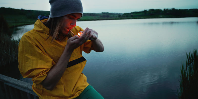 Man smoking a joint in front of a beautiful landscape
