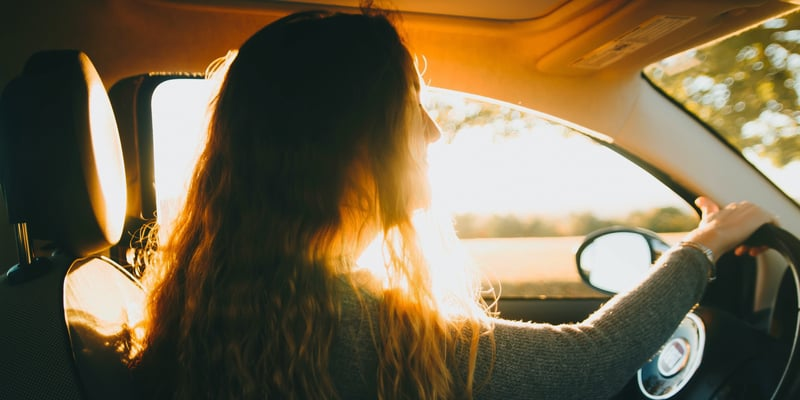 Girl driving car, lit by sunlight, using vaporizers that you can charge in the car