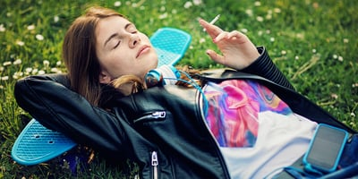 Teenage girl is lying down and enjoying a smoke session
