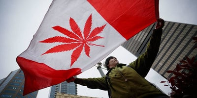 A pot supporter holds up a flag to celebrate The Cannabis Act Just Got Royal Assent: Weed Will Be Legal on October 17th